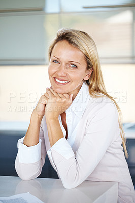 Buy stock photo Portrait of a pretty young businesswoman sitting by the desk in office