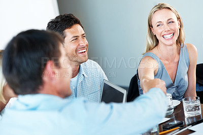 Buy stock photo Portrait of business partners shaking hands at business meeting with a smiling businessman sitting near by