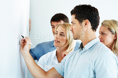 Buy stock photo Smart young businessman giving a presentation to his business colleagues in the office