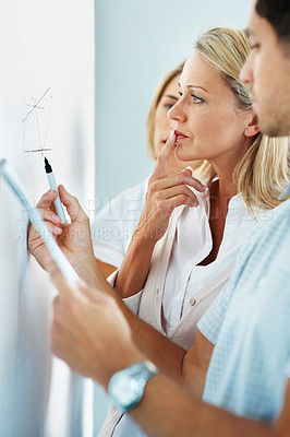 Buy stock photo A business team analyzing a graph on a whiteboard