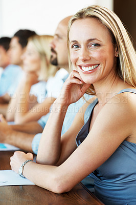 Buy stock photo Portrait of a beautiful young businesswoman smiling at you, with her colleagues sitting in a row in the background