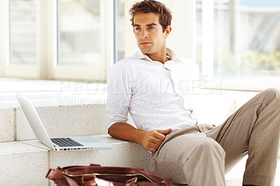 Buy stock photo Smart young businessman sitting on steps looking away with laptop