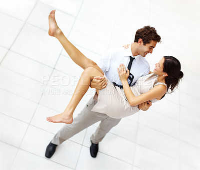 Buy stock photo Top view of happy young businessman carrying his cute girlfriend in his arms