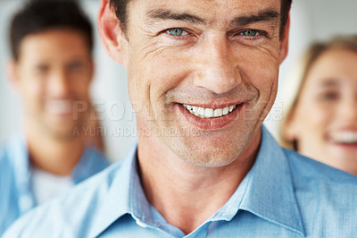 Buy stock photo Closeup portrait of handsome mature man smiling with people in background