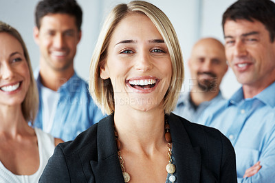 Buy stock photo Portrait of a confident young businesswoman smiling with her business colleagues behind her