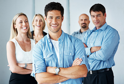 Buy stock photo Portrait of a smart businessman standing with folded arms with his business team in background