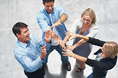 Buy stock photo Top view of business team enjoying success with their hands raised