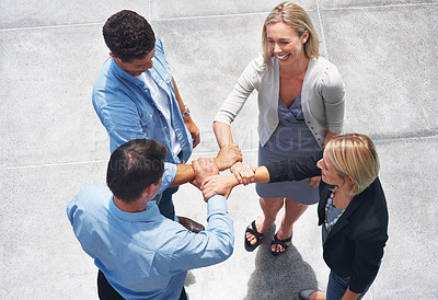 Buy stock photo Top view of small group of business people joining hands and smiling