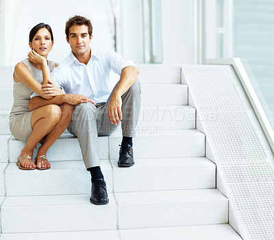 Buy stock photo Portrait of attractive young couple sitting together on stairs of a building