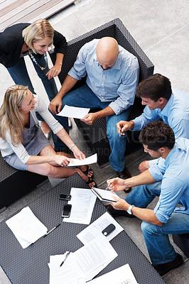 Buy stock photo Top view of a team of business people sitting together and discussing project