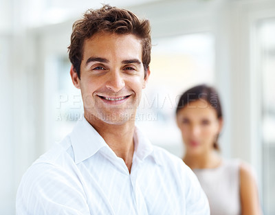 Buy stock photo Portrait of handsome young man smiling with a female in background