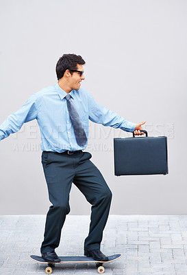 Buy stock photo Male executive on skateboard with briefcase in hand