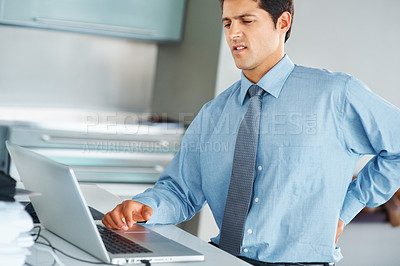 Buy stock photo Portrait of young executive holding back with pain at office