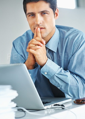 Buy stock photo Serious executive sitting in front of laptop