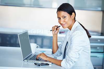 Buy stock photo Female executive working on laptop with cell phone nearby