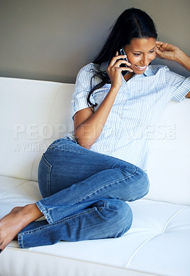 Buy stock photo Attractive woman on cell phone while curled up on sofa