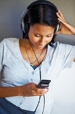 Buy stock photo Pretty woman listening to headphones through cell phone while sitting on sofa