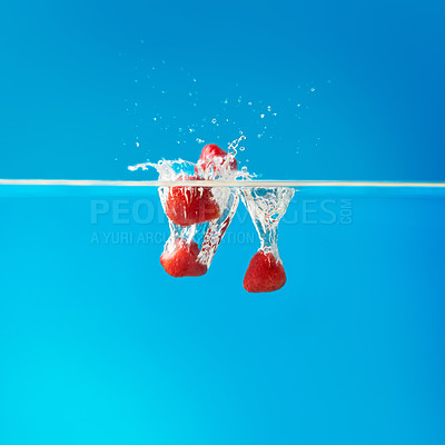 Buy stock photo Strawberries dropped into water against blue background