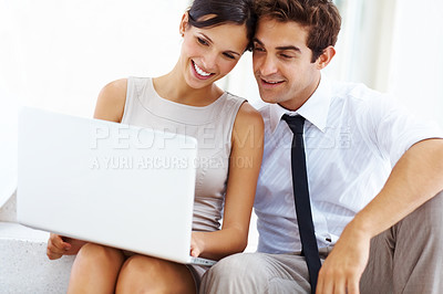 Buy stock photo Handsome young businessman sitting with his girlfriend using laptop