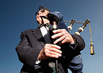 Mature highlander wearing kilt and playing bagpipes against sky