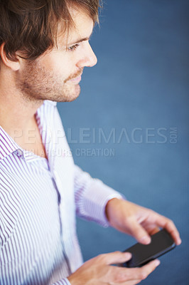 Buy stock photo Side view of young business man holding cell phone on blue background
