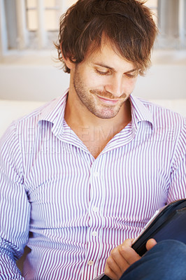 Buy stock photo Happy young man smiling while looking at portfolio