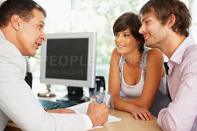 Buy stock photo Consultant showing new investment plans to young couple