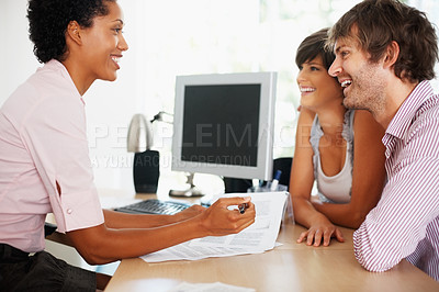 Buy stock photo Smiling young couple listening to female consultant