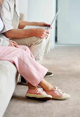 Buy stock photo Waist down shot of an elderly couple sitting on a sofa and using a laptop