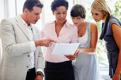 Buy stock photo Team leader explaining report to his team