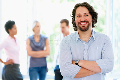 Buy stock photo Man standing with arms folded while group has discussion in background