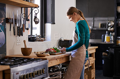 Buy stock photo Shot of a young woman chopping vegetables at a kitchen counter