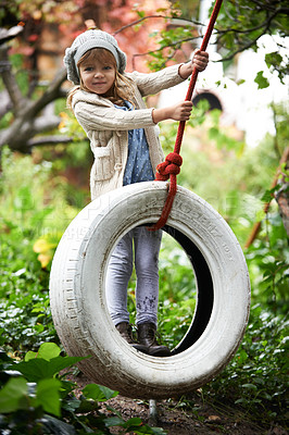 Buy stock photo Portrait of a cute little girl playing on a tire swing in the garden