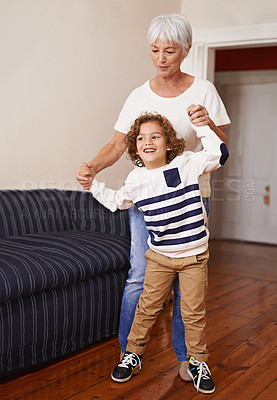 Buy stock photo Shot of a little boy and his grandmother being playful indoors