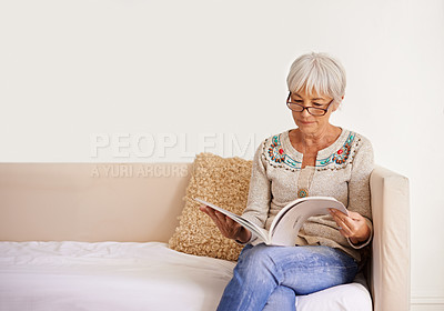 Buy stock photo Shot of a senior woman reading a book while sitting on a sofa