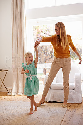 Buy stock photo Full-length shot of a young woman playfully dancing with her little girl