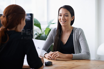 Buy stock photo Shot of two young professionals having a discussion at a desk