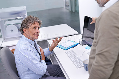 Buy stock photo A mature businessman sitting at his workstation explaining something to his colleague