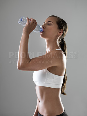 Buy stock photo Shot of a young woman drinking water  during her workout