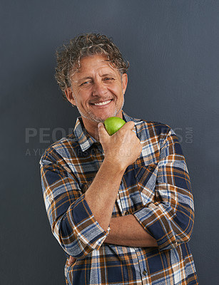 Buy stock photo A portrait of a happy mature man holding a delicious apple