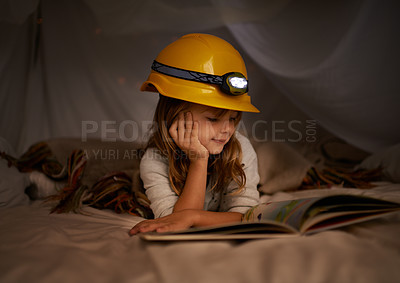 Buy stock photo Shot of an adorable little girl using a headlight to read her book in a fort
