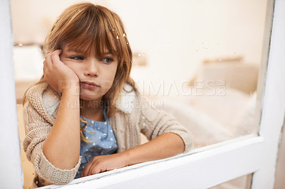 Buy stock photo Shot of a bored-looking little girl sitting and looking out a window on a rainy day