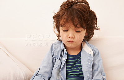 Buy stock photo Shot of an unhappy-looking little boy sitting indoors