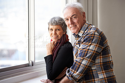 Buy stock photo Portrait of a senior couple enjoying an affectionate moment by the window