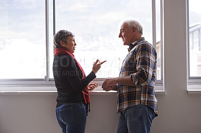 Buy stock photo Shot of a senior couple having a discussion in front of a window