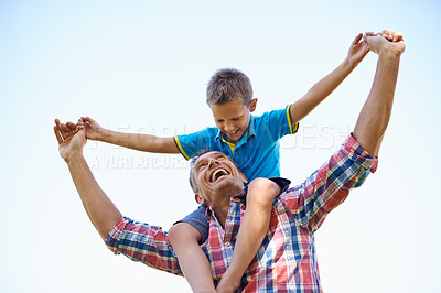 Buy stock photo A low angle shot of a happy father carrying his young son on his shoulders