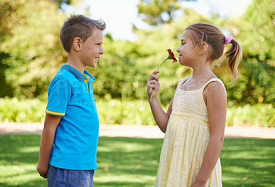 Buy stock photo A little girl happily holding the flower given to her by a cute boy with a crush