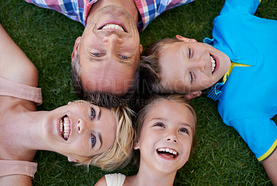 Buy stock photo A cropped high angle shot of a happy family lying on the grass with their heads together