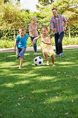 Buy stock photo A happy family playing soccer in the park on a beautiful summer day