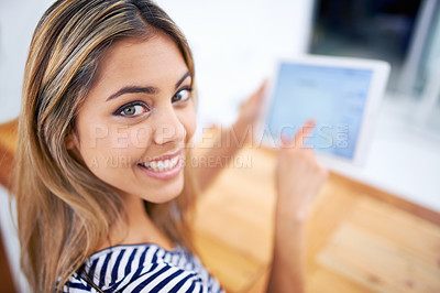 Buy stock photo A cropped portrait of a beautiful young woman using a tablet at her desk